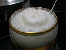 Gold rimmed glass with fresh frothy beer. Close up view Stock Photos
