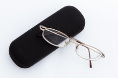 Gold rimmed glasses on black case. Gold rimmed glasses leaning a black case on a white background Royalty Free Stock Photos