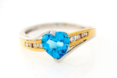 Gold ring with blue sapphire heart shaped. And with diamonds on a white background royalty free stock photography