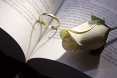 Gold ring and book a romantic heart forming Stock Photos