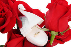 Gold ring in a box in the form of a swan on red roses Stock Photos