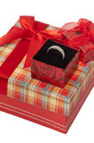 Gold ring in a box on a red box with a beautiful bow Royalty Free Stock Photo