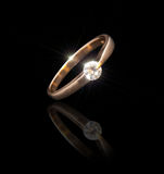 Gold ring with a brilliant. On a black background Stock Photos