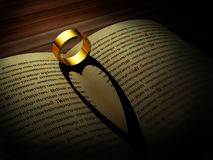 Gold ring casts shadow of a heart Stock Image