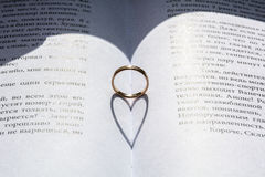 Gold ring in the centre of book with the heart shape shadow Royalty Free Stock Photography