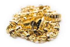 Gold ring and chains. Two gold rings over gold chains over white background royalty free stock photos