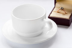 Gold ring with a diamond and a cup and saucer Royalty Free Stock Photography