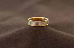 Gold ring with diamonds. Close up of elegant diamond ring with cloth background Royalty Free Stock Image