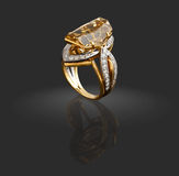 Gold ring with diamonds and gem. On grey Stock Photography