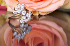 Gold ring with diamonds and pink rose. Rose and ring form a reflection on the mirror surface Royalty Free Stock Image