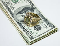 Gold ring on dollar bills Royalty Free Stock Images