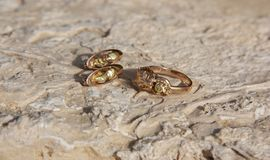 Gold ring and earrings lie on the stone surface royalty free stock photography