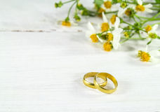 Gold ring and flower on wood background Stock Photos