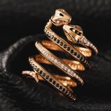Gold ring in the form of kissing snakes with cubic zirconias and black diamonds on a leather background. Close-up stock photos