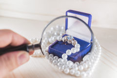 Gold ring with gem in a blue gift box and pearl beads Stock Images