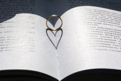 Gold ring with the heart shape shadow on russian book Royalty Free Stock Photos