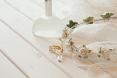 Gold ring and necklace, white floral tiara and perfume bottle. On toilette table. Selective focus Royalty Free Stock Photos