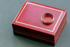 Gold ring. A plain gold wedding ring or band, placed on a red jewellery box Stock Images