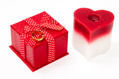 Gold ring with a red box with a red bow and heart candle Stock Photos