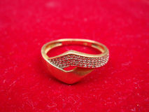 Gold ring. On red surface Royalty Free Stock Photos