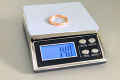 The gold ring on the scales Stock Image