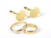 Gold rings. And cuff links on white in studio Royalty Free Stock Photo