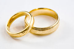 Gold Rings. 2 Gold wedding rings one for a man and one for a woman Royalty Free Stock Photos