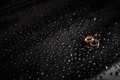 Gold rings on a black background royalty free stock images