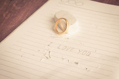 Gold rings on book. Love never fades Royalty Free Stock Photo