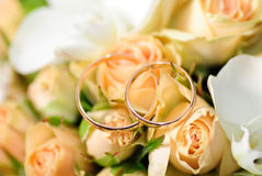 Gold rings on a bouquet of roses Royalty Free Stock Images