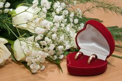 Gold rings are in box and bouquet of roses. Stock Photos