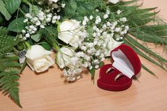 Gold rings are in box and bouquet of white roses. Royalty Free Stock Photography