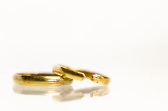 Gold rings broken. 2 gold wedding bands but one is cut apart Royalty Free Stock Photos