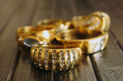 Gold rings closeup. Various decorated gold rings over wood surface Stock Photos