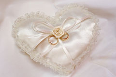 Gold rings on cushion. Two gold wedding rings on a cushion heart shaped made from white silk royalty free stock photo