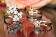 Gold rings with diamonds and pink rose. Gold rings with diamonds on a mirrored background. In the background rose, which is reflected on the surface Royalty Free Stock Image