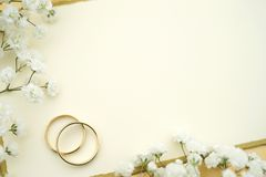 Wedding Invite. Gold rings with empty card and flowers Royalty Free Stock Images