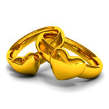 Gold rings with heart shape. Gold wedding rings with heart shape on white background royalty free stock image