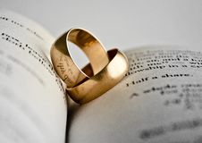 Gold rings on the pages of the book. The reflection of the words in the rings royalty free stock photo