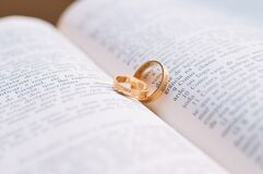 Gold rings on pages of an open Bible Stock Photos