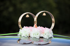 Gold rings and rose flowers on wedding car Stock Photo