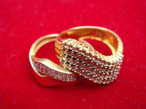 Gold rings. Two gold rings on red surface stock images