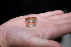 Gold rings for wedding are on the palm of the groom Stock Photography