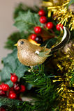Gold robin and holly Christmas decorations. Festive Christmas close up of tree decorated with gold glitter robin, tinsel and holly berries. Vertical royalty free stock images