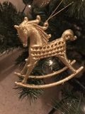 Gold rocking horse Christmas ornament on tree Stock Photography