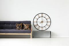 Gold round clock in room. Gold, round clock on metal bench next to a black, wooden settee with brown cushions in living room interior Stock Photo