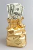 Gold sack full of dollars on gray Royalty Free Stock Photos