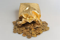 Gold sack with scattered coins on gray Royalty Free Stock Photo