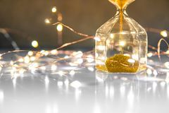 Hourglass on glossy table with decorative lights stock photography