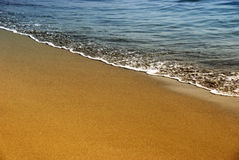 Gold sand and sea foam Royalty Free Stock Photo